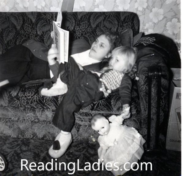 Mom and me (age 2 0r 3) reclining on the couch reading a picture book. I'm holding a doll. Black and white photo.