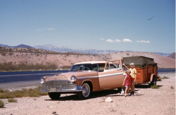 My little sister (age 5?) and I (age 9 or 10) standing beside an old model (new at the time!) Chrysler (?) that is parked by the side of a highway in the desert and is pulling a trailer filled with our worldly posessions. We are on our way to California from the Midwest.