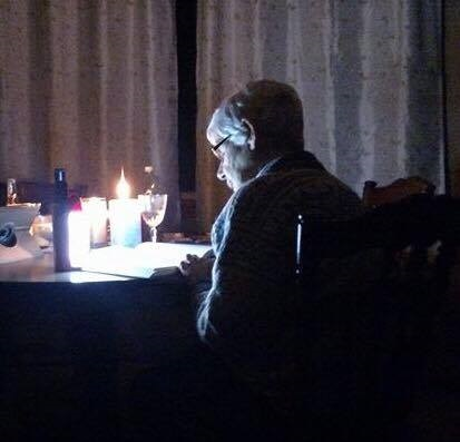 My Aunt Myla reading at her kitchen by candlelight during a power outage