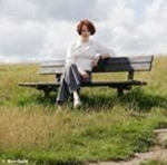 Author Maggie O'Farrell (image: sitting on a wooden bench in the middle of a field)