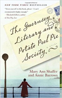 The Guernsey Literary and Potato Peel Pie Society y Mary Ann Shaffer (cover) Image: black text on a postcard....a woman dressed in a red coat stands at a railing overlooking the ocean