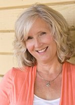 Author, Susan Meissner (head shot, wearing a coral cardigan leaning against a wood slat wall)