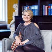 Author Veronica Henry (sitting casually on the end of a sofa with legs curled up)