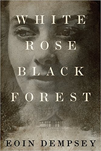 White Rose Black Forest by Eoin Dempsey (cover) Image: a grayscale image of a cabin in the woods and a woman's face filling the background