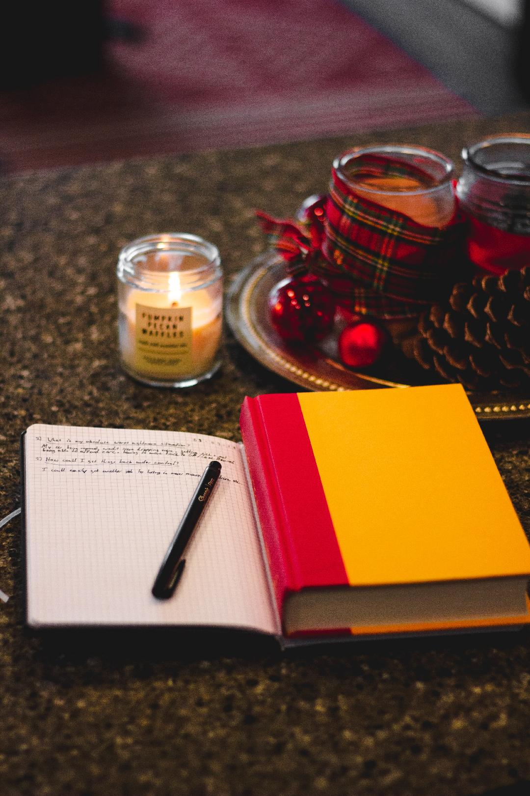 an open journal and pen next to a hardback book and a candle (also, plaid ribbon and red ornament decorations on a silver tray)