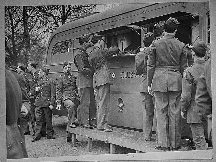 a black and white picture of servicemen lined up at a Clubmobile window