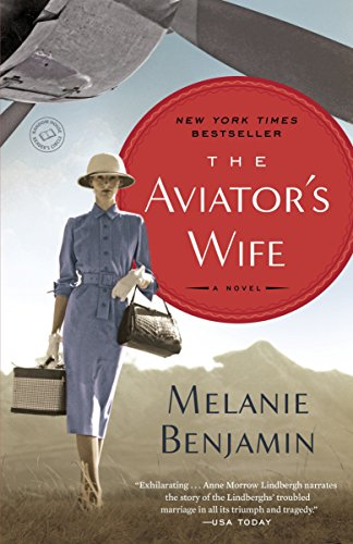 the Aviator's Wife by Melanie Benjamin (cover) Image: a woman wearing a hat and in a blue dress (holding a purse and a travel bag) walks beneath the propeller of a small aircraft