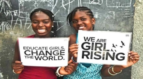 Two Nigerian girls holding signs: Educate Girls. Change the World and We are Girl Rising