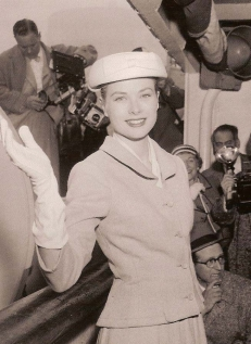 Grace Kelly smiling and waving (wearing white gloves)