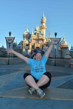 Abby seated (arms thrown in the air) with Cinderella's Castle in the background