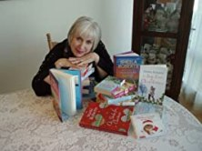 Author Sheila Roberts sits with her books at a dining room table