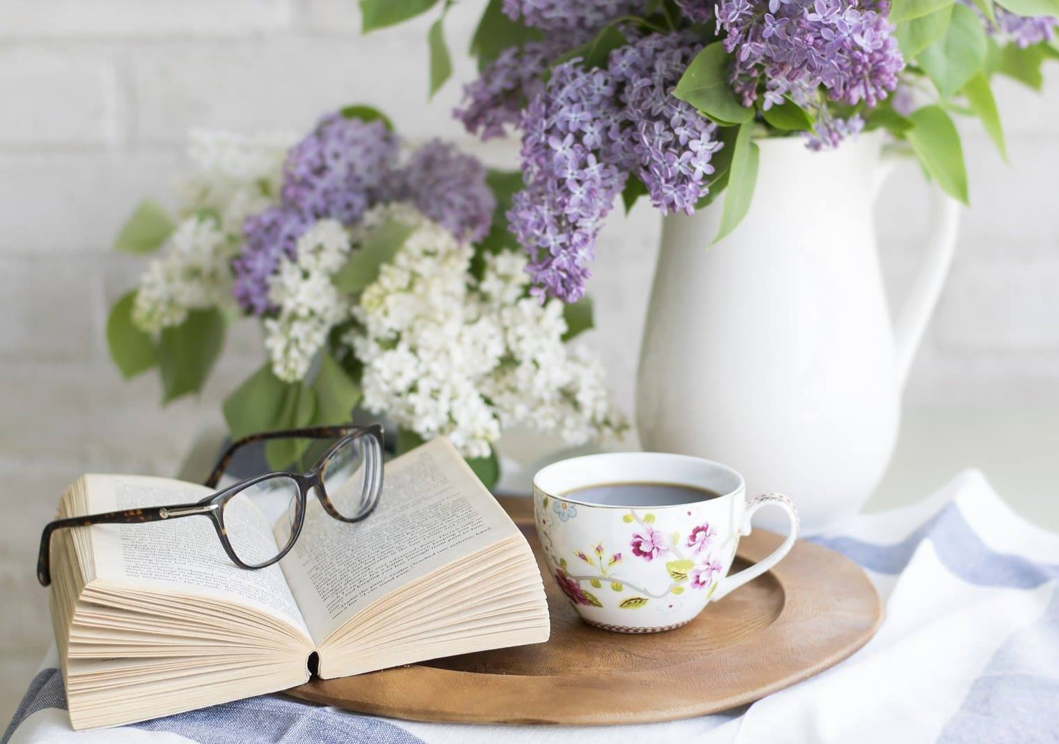Swirl and Thread blog header (a white pitches filled with purple and white lilacs, a tea cup, glasses resting on an open book)