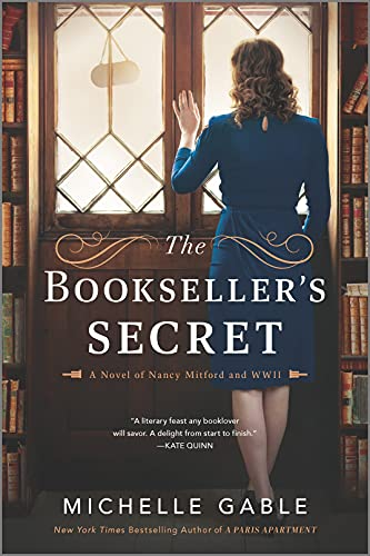 The Bookseller's Secret by Michelle Gable (cover) Image: a young woman in a blue dress stands with her back to the camera looking out a set of windows