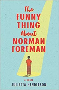 The Funny Thing Aboout Norman Foreman by ???? (cover) Image: a man wearing a red t shirt and brown pants stands in an elongated yellow spotlight