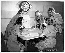 Women's Air Raid Defense: five women from WW11 sit around a table looking at charts