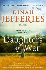 Daughters of War by Dinah Jefferies (cover) Image: a woman stands with her back to the camera in a field with trees and a house on a hill in the distance