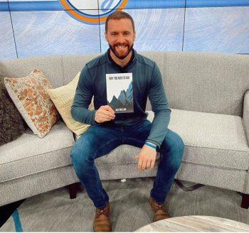 Author Jake Kneeland sits on a couch holding a copy of Why You Need to Fail
